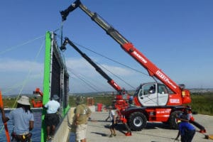 Mobile cranes hold up green screens for outdoor film shoot
