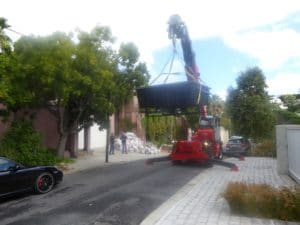 Our mobile crane telehandler lifting a swimming pool over a garage and phone line - Liftup Teleporter