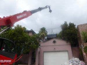 A mobile crane telehandler placing a swimming pool in position after lifting it over a telephone line - Liftup Teleporter