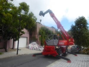 A mobile crane telehandler lifting a swimming pool over a telephone line - Liftup Teleporter