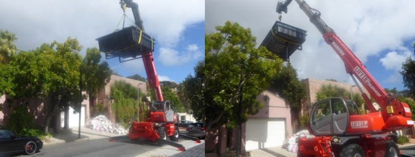 Mobile crane telehandler lifting a swimming pool over a wall