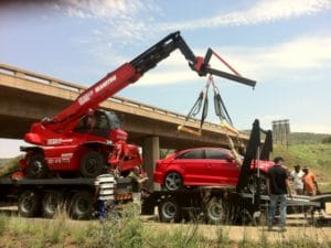 Mobile crane lifts car in TV film shoot.