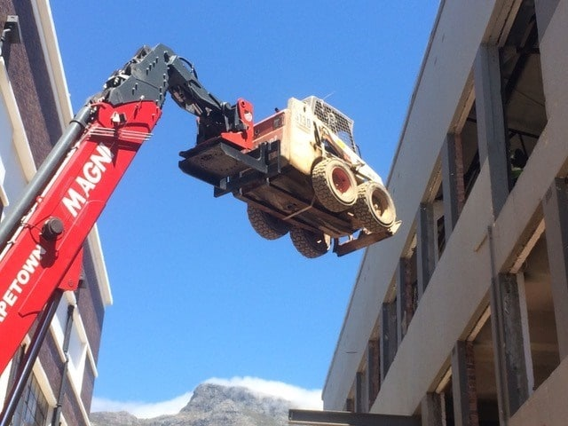 Using a mobile crane to lift a bobcat onto a building site