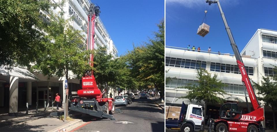 Telehandler lifts load in narrow street