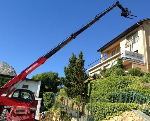 Mobile crane lifting bricks up a slope