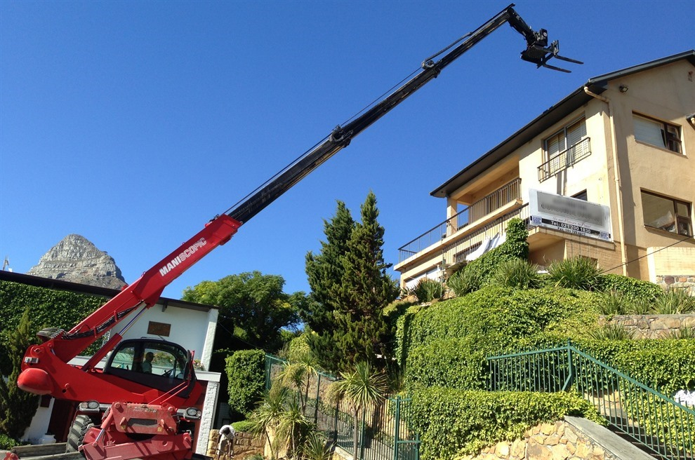 Telehandler mobile crane lifting bricks up a slope