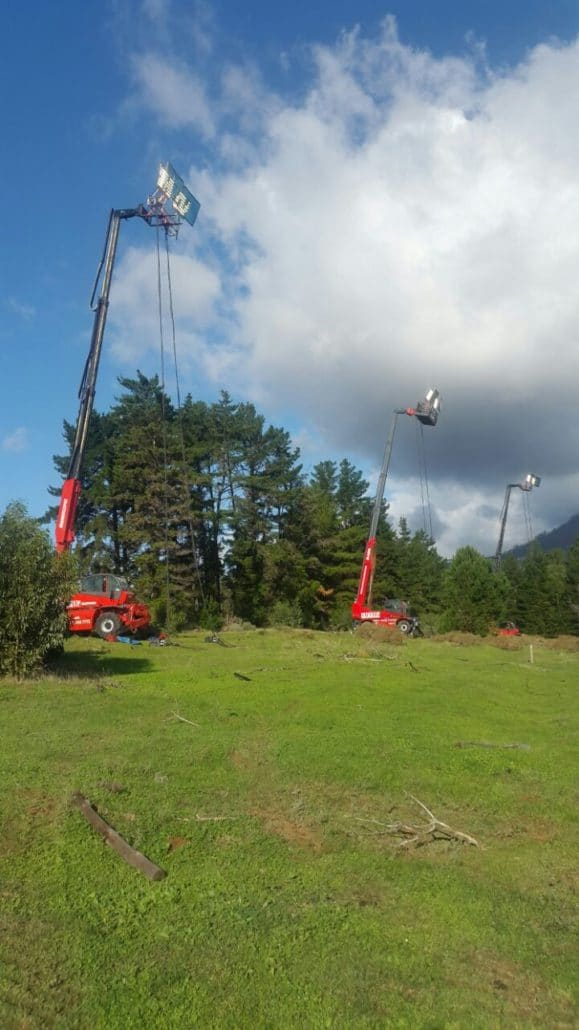 Three mobile cranes holding up lighting at an outdoor film shoot