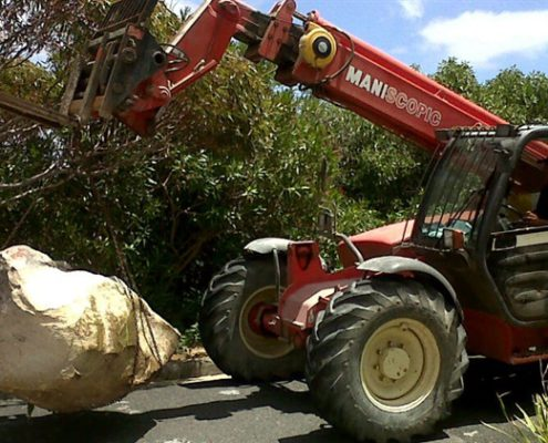 The Manitou telehandler carrying rocks from a building site.
