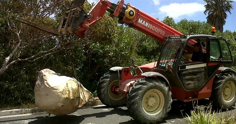 The Manitou MT 1033 telehandler carrying rocks from a building site.
