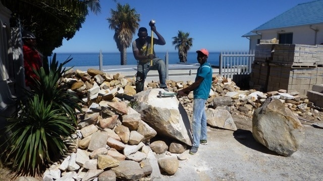 The stonemasons cutting down the boulders to workable size.