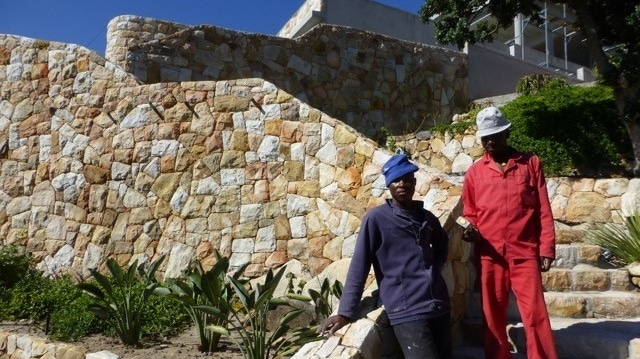 Stonemasons stand next to a stone wall they have built