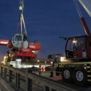 Using a Liebherr crane to lift a Manitou mobile crane into an empty canal.