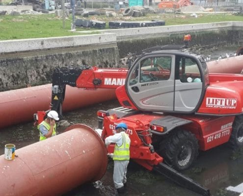 A Manitou 2150 mobile crane laying pipes in a canal
