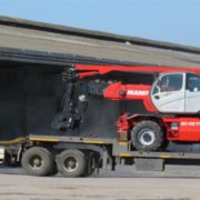 Hired mobile crane transported on flat bed truck
