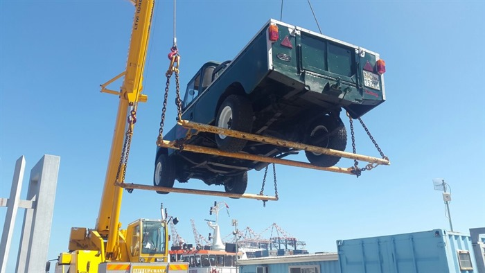 Liebherr crane loading a car onto a boat