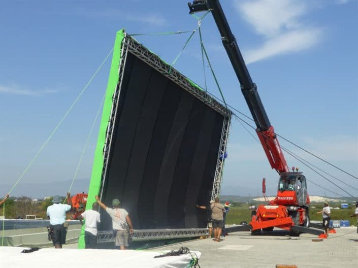 Mobile cranes carrying green screens on movie set