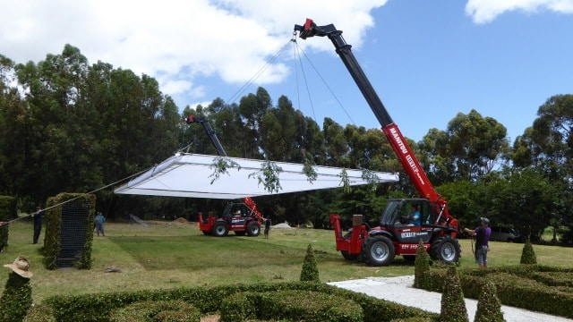 Mobile cranes carrying shade screens on movie set