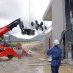 Mobile crane lifting heavy glass