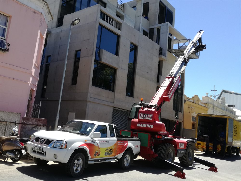 Mobile crane lifting furniture from the street