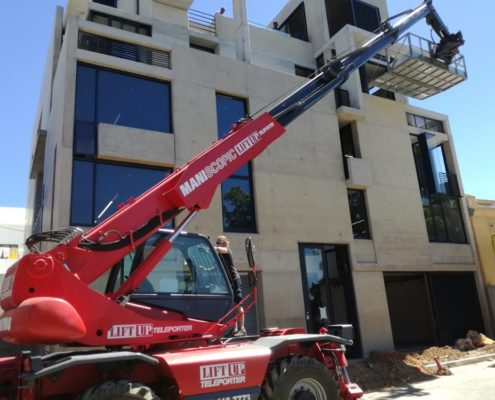 Mobile crane lifting furniture to apartment