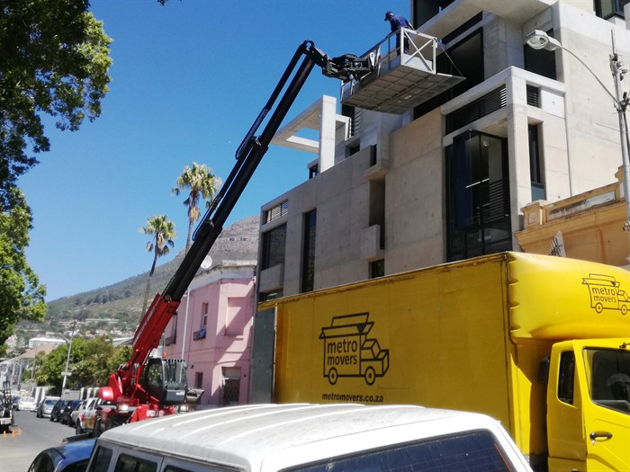 Mobile crane lifting furniture into apartment